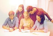 Smiling students with notebooks at school Stock Photos