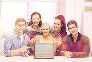 Smiling students pointing to blank lapotop screen Stock Photos