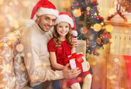 Smiling father and daughter holding gift box Stock Photos