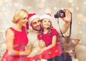 Smiling family in santa helper hats taking picture Stock Photos