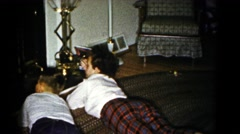 1959: two little boys lie in front of a lit fireplace on a cold day. HAGERSTOWN Stock Footage
