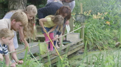 4K Families at conservation center, children with fishing nets exploring pond Stock Footage