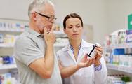 Pharmacist showing drug to senior man at pharmacy Stock Photos