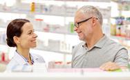 Happy pharmacist talking to senior man at pharmacy Stock Photos