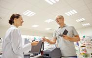 Senior man giving money to pharmacist at drugstore Stock Photos