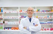 Senior male pharmacist in white coat at drugstore Stock Photos