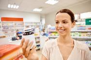 Happy female customer with drug jar at pharmacy Stock Photos