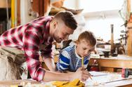 Happy father and son with blueprint at workshop Stock Photos
