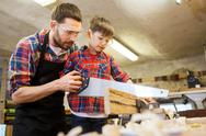 Father and son with saw working at workshop Stock Photos