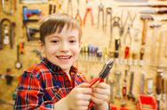 Happy little boy with pliers at workshop Stock Photos