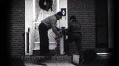 1959: a pair of people decorating the front of their house with ornaments Stock Footage
