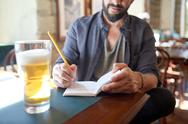 Close up of man with beer and notebook at pub Stock Photos