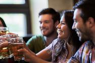 Happy friends drinking beer at bar or pub Stock Photos