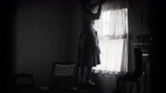 1959: woman in an apron hanging christmas decorations on a window frame Stock Footage