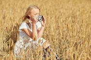 Woman taking picture with camera in cereal field Stock Photos