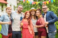 Happy friends with drinks at summer garden party Stock Photos