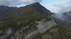 CINEMATIC FLY OVER OF FIELDS ON STEEP ROCK CLIFFS IN SWISS ALPS Stock Footage