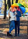 Loving couple on date under umbrella. Stock Photos