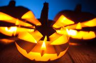 Three jack-o-lantern pumpkins glowing in the dark Stock Photos