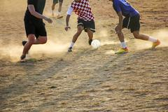 Young boys playing football game on the sunset Kuvituskuvat