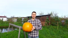 Cheerful countryman take and carry large orange pumpkin, walk towards camera Stock Footage