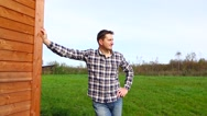 Handsome rustic man stand against house put hand on hip and look at distance Stock Footage