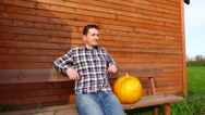 Thoughtful farmer sit on a bench with big pumpkin, look at distance Stock Footage