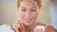 Middle-aged blond woman putting cosmetics on Stock Footage