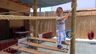 Small boy jumps on rope ladder Stock Footage