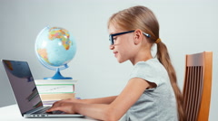 Portrait schoolgirl four-eyes typing in her laptop sitting at desk isolated Stock Footage
