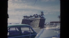 1962: statues, cars, and people fill the parking area outdoor a stadium  Stock Footage