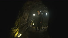 4K Team of potholers with hard hats and lamps exploring underground cave system Stock Footage