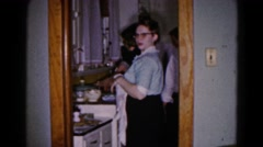1959: a lady standing in the kitchen closes the door of cupboard HAGERSTOWN Stock Footage