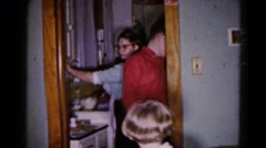 1959: a family is busy preparing dinner and a boy points out his infant sibling Stock Footage