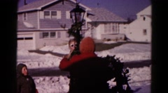 1959: a family outdoor in the snow decorating a light post for christmas Stock Footage