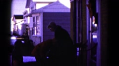 1959: a family on the front porch of a house bundling up for the cold weather Stock Footage