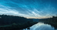 Timelapse of noctilucent clouds over a forest and river Stock Footage