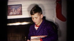 1959: a young boy opening and inspecting one of her presents in christmas Stock Footage
