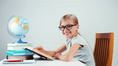 School girl four-eyes reading textbook and laughing at camera Stock Footage