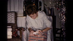1959: a young woman gingerly opens a package  Stock Footage