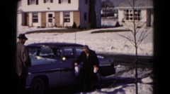 1959: elderly lady carrying packages walks gingerly through the snow past a car Stock Footage