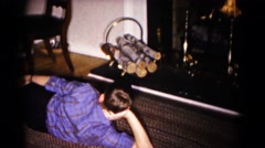 1959: boy reclining on floor watching holiday fireplace display HAGERSTOWN Stock Footage
