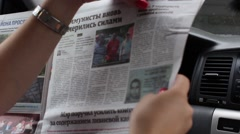 Woman reads the morning newspaper while sitting in the car Arkistovideo