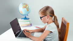 School girl four-eyes typing in her laptop and smiling at camera Stock Footage