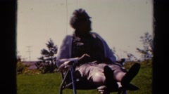 1962: an elderly woman sits in a lawn chair in a grassy area on a chilly day Stock Footage
