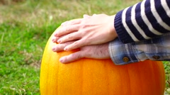 Man put hand on bright orange pumpkin, woman palm touch softly over Stock Footage