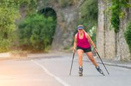 Beautiful sporty blonde girl with Rollerblade and climbing sticks Stock Photos