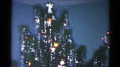 1962: a group of young posing in front of a christmas tree with many decorations Stock Footage
