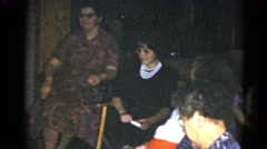 1962: women sit in chairs in a semicircle as a girl brings them presents Stock Footage