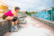 Sporty girl you change to make rollerblade on the steps of the field Stock Photos